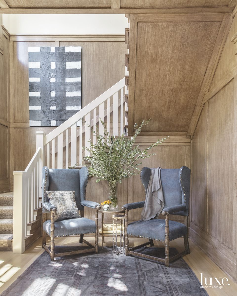 Corner Staircase Sitting Area With Blue Wingback Chairs and Wood Paneling