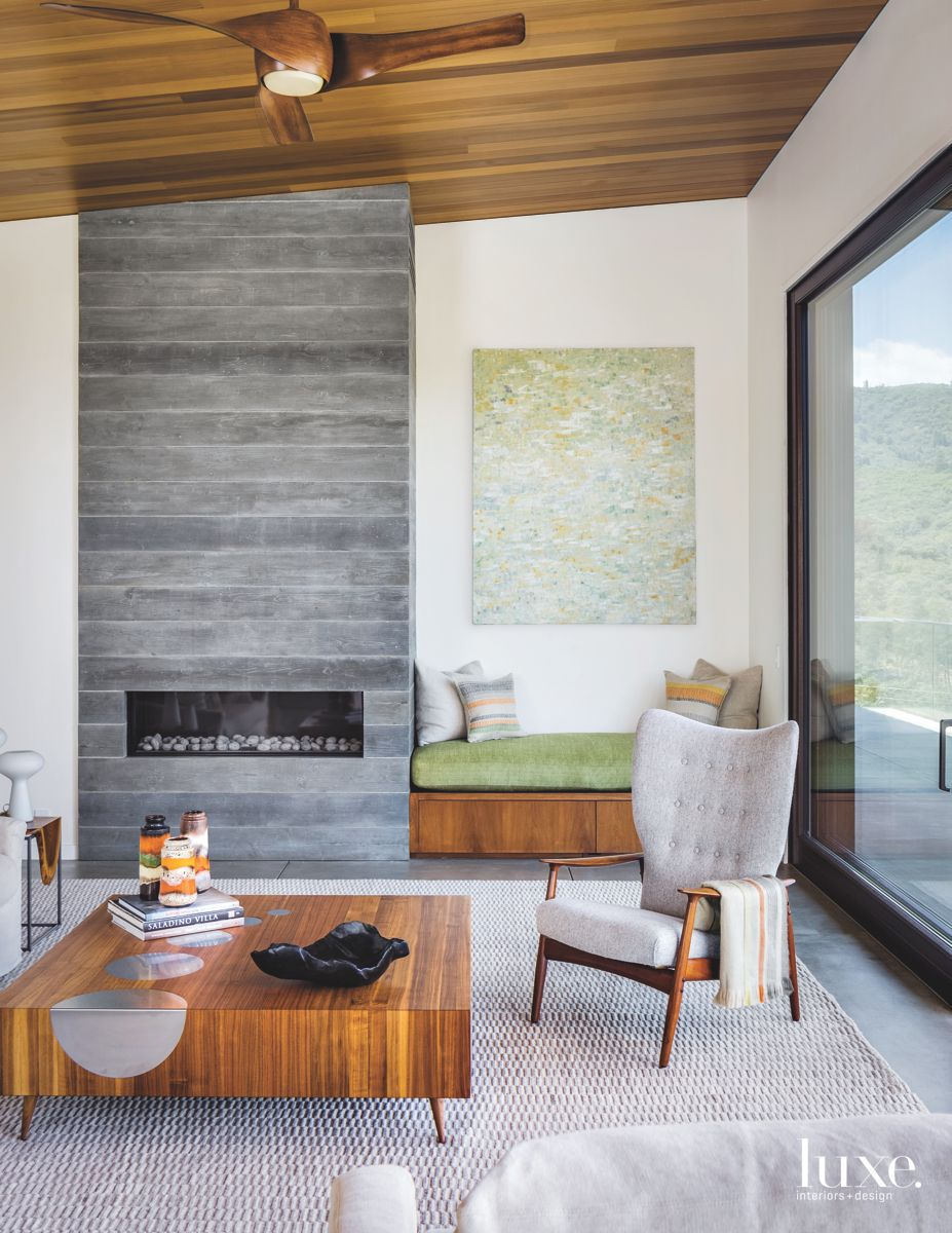 Walnut-Accented Living Area with Stone Fireplace and Artwork