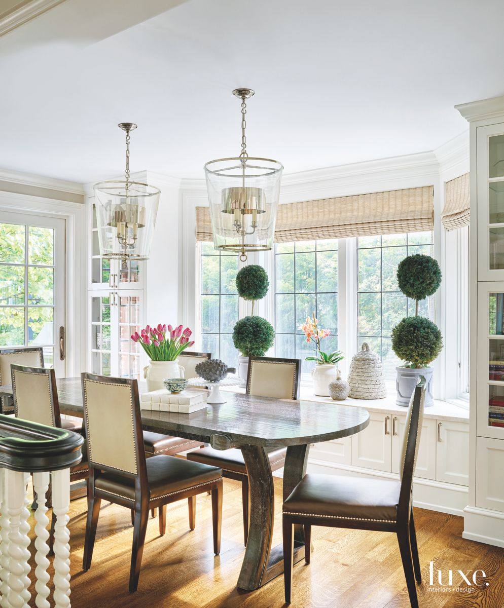 Large Lantern Chandelier Dining Area with Window Sill and Neutral Chairs