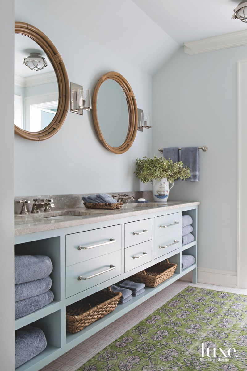 Blue Guest Bathroom with Circular Twin Mirrors and Green Patterned Rug