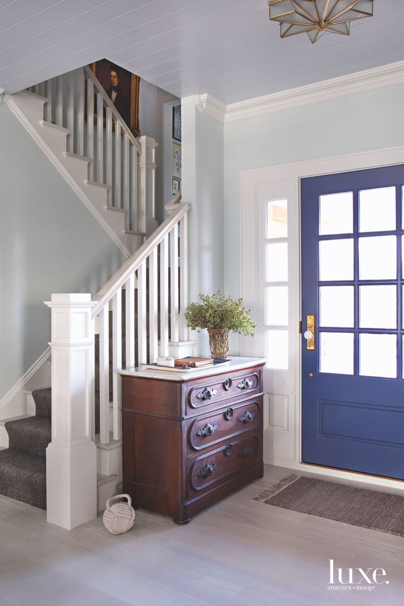 Blue Door and Blue Entryway with Traditional Staircase and Chest
