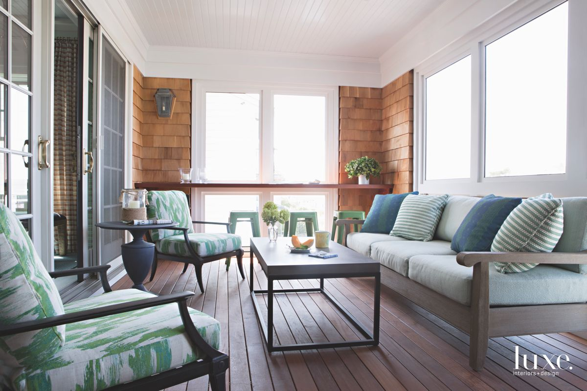 Enclosed Porch with Shingle Siding and Green Cushion Furniture